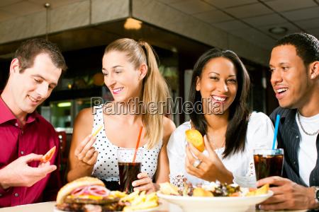 amici di mangiare hamburger e bere