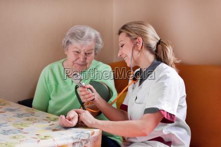 altenpflegerin misura la pressione sanguigna a